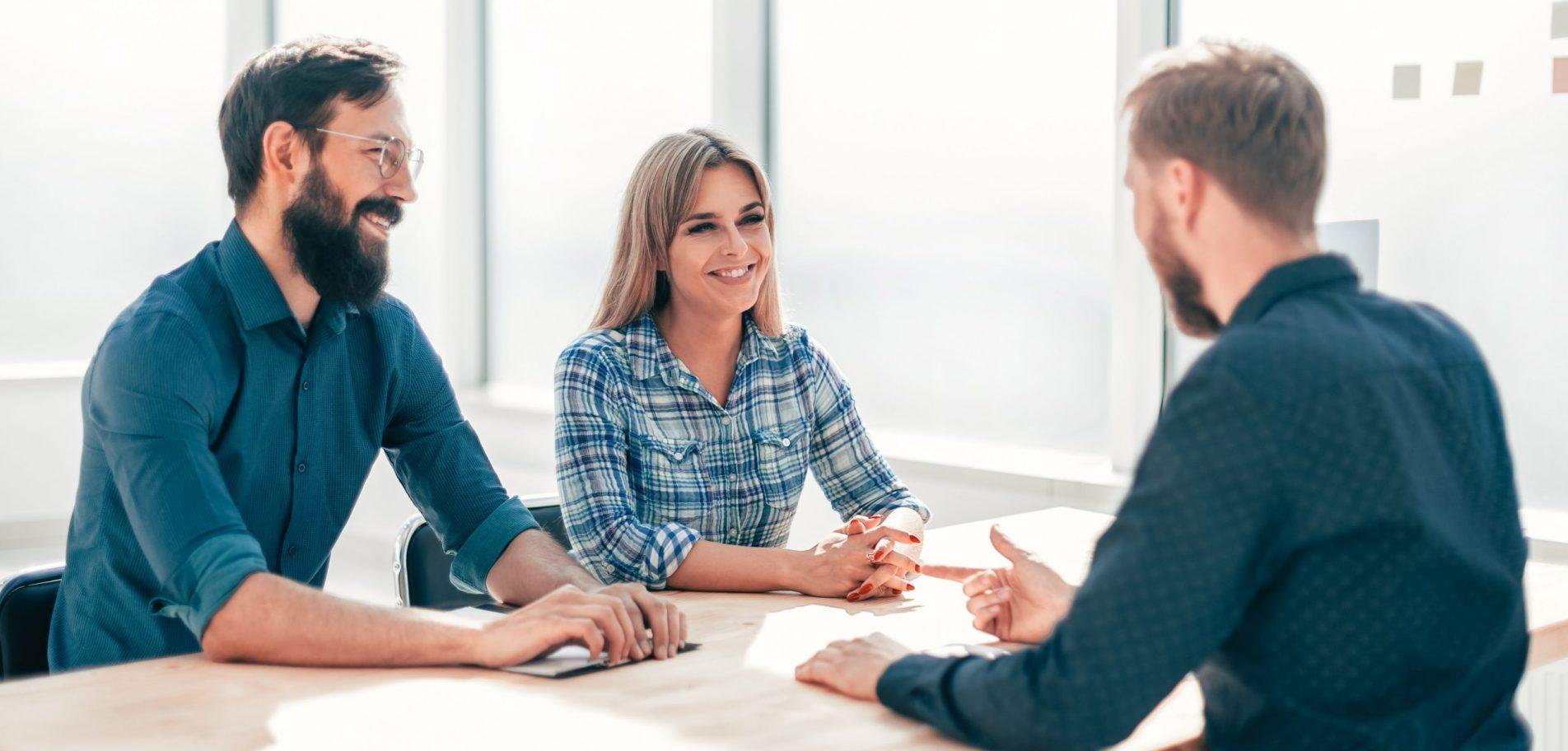 Un réviseur et des coopérateurs assis autour d'une table qui échangent sur le dossier de leur entreprise coopérative